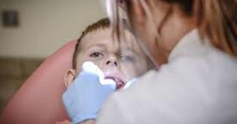 Стоматологический гигиенист работает с ребенком