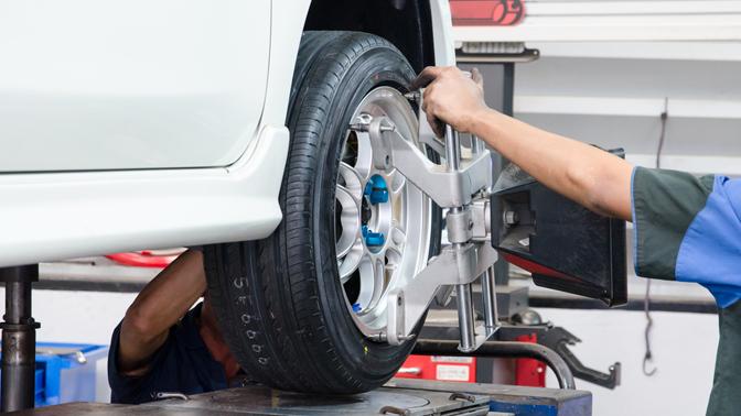 Мастер шиномонтажа меняет колесо на автомобиле