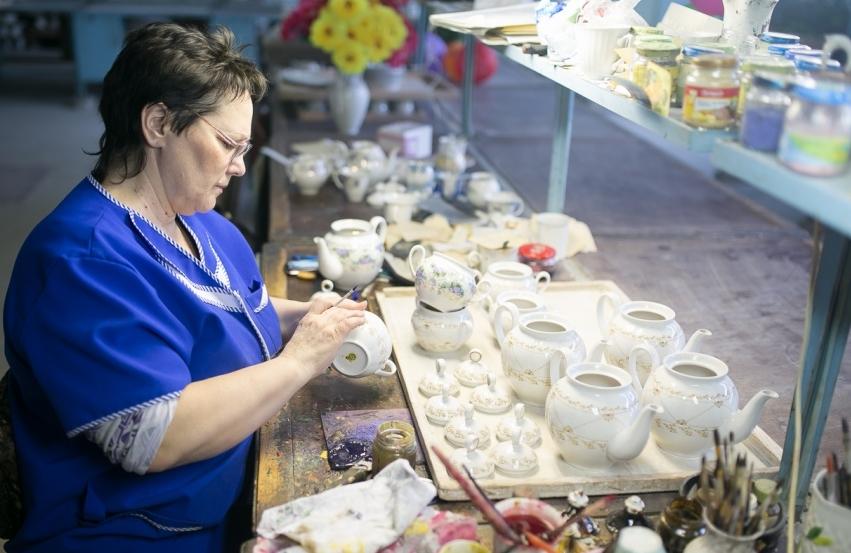 Женщина рисует на чашках