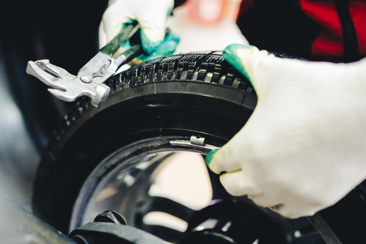 Мастер занимается починкой автомобильной шины