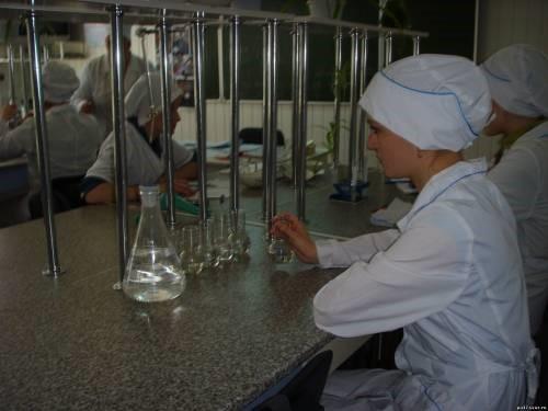Девушка-лаборант разливает жидкость в пробирки