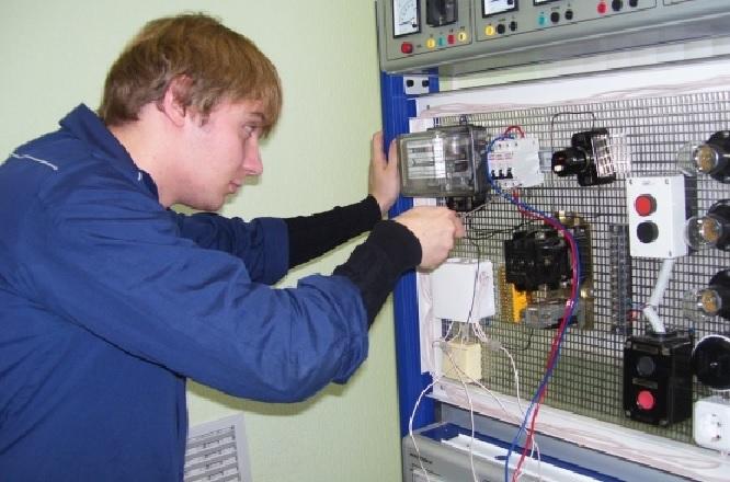 Молодой специалист работает с трансформатором