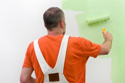 Мастер-маляр занимается покраской поверхности