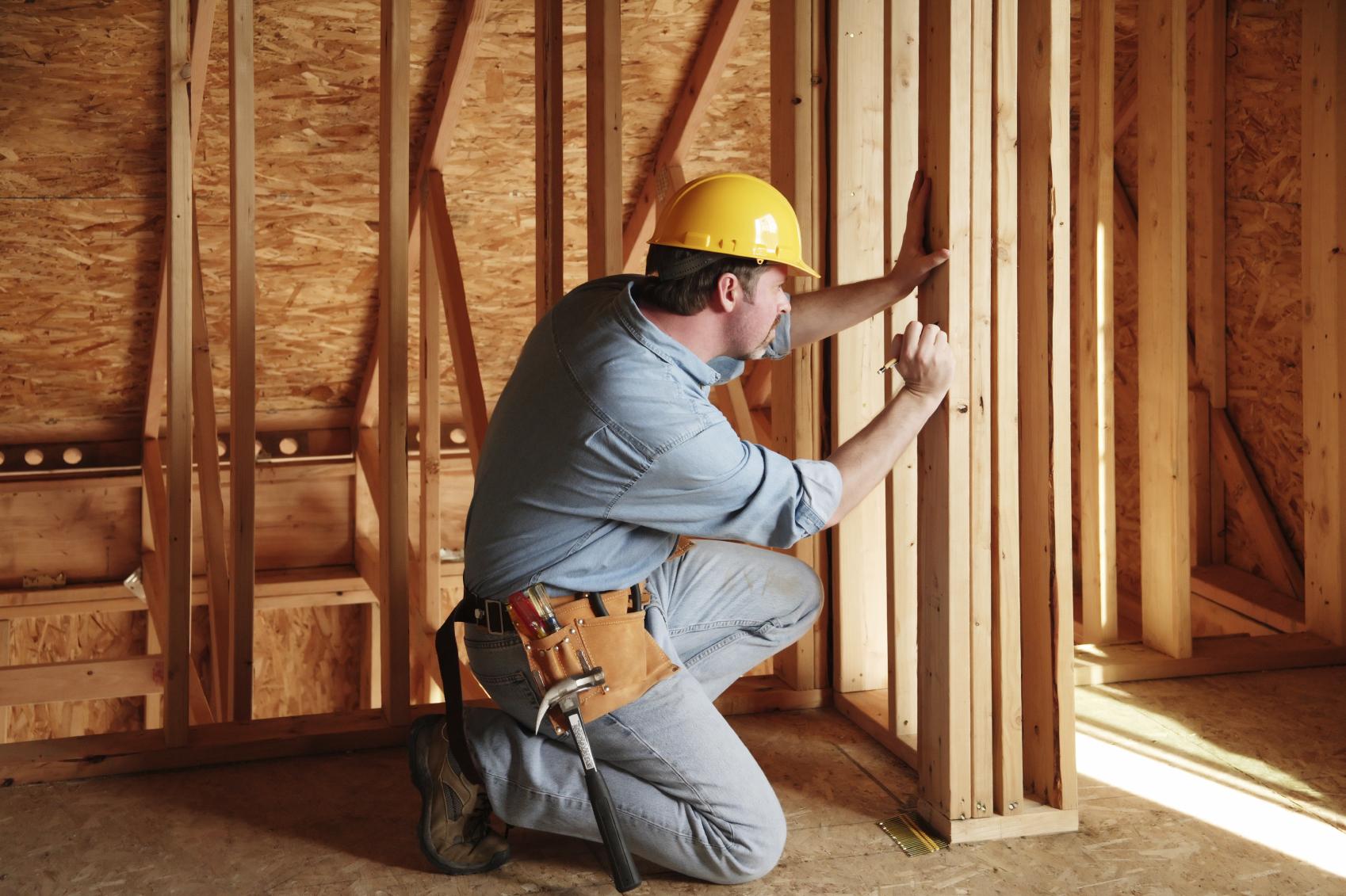 Мастер столярно-плотничных работ производит разметку на конструкции