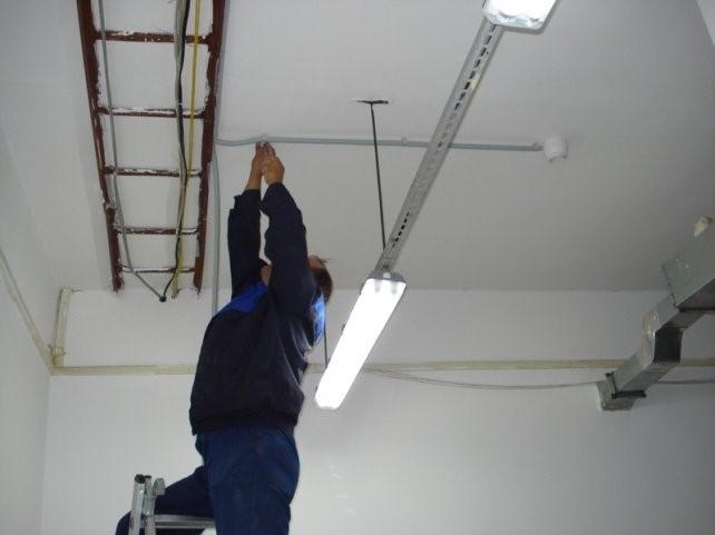 Мужчина проверяет пожарную сигнализацию