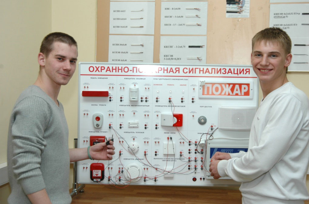 Молодые парни у стенда по охранно-пожарной сигнализации