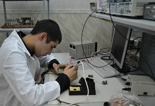 молодой человек паяет компьютерную плату