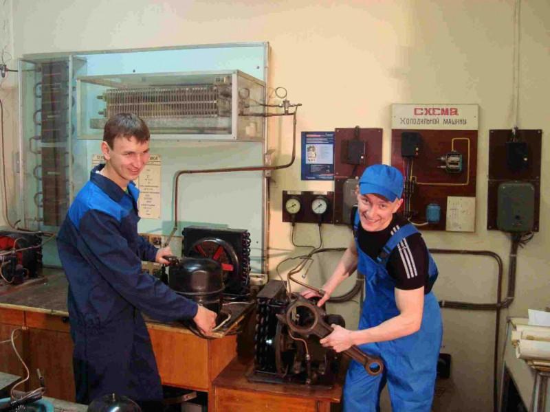 Два молодых специалиста занимаются ремонтом оборудования