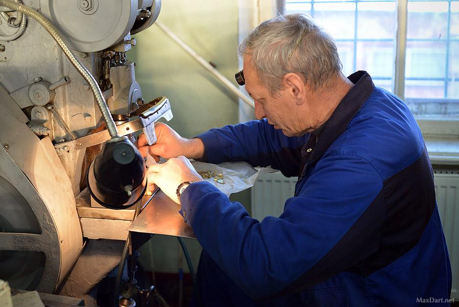 Мужчина работает с мелкими деталями часовых механизмов