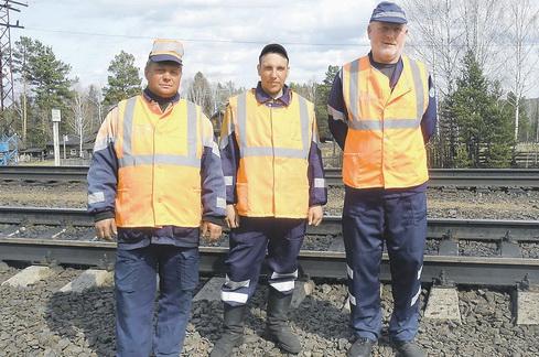 Железнодорожные рабочие стоят на рельсах