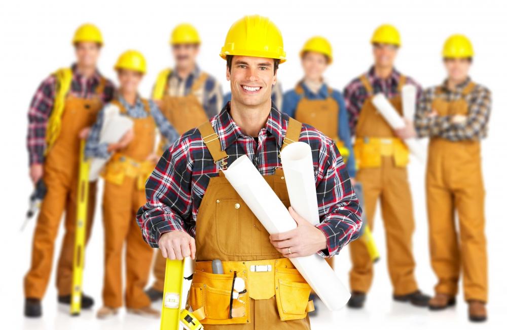 Строители в касках и один с проектами под мышкой