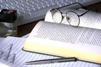 Книга и очки в процессе составления диссертации