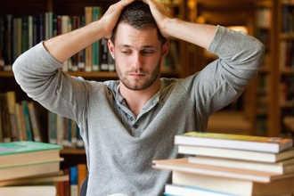 Человек смотрит на большую стопку книг