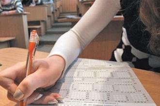 Девушка заполняет бланки для сдачи ЕГЭ