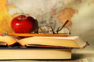 Книги, яблоко и очки лежат на столе