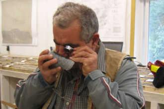 Геолог изучает керн под микроскопом