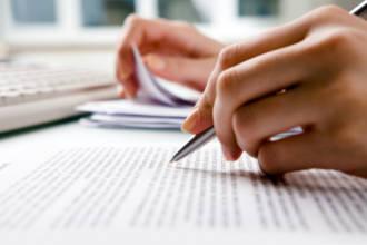 Рука и ручка над текстом