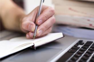 Ноутбук, и ручка в руке