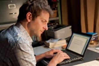 Мужчина печатает тексты на компьютере