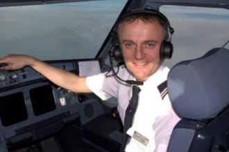 Летчик позирует для фото в кабине самолета