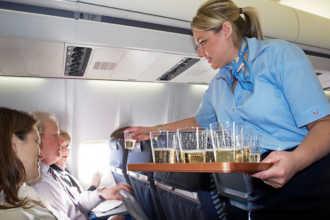 Стюардесса раздает напитки пассажирам