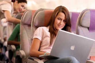 Девушка в самолете использует ноутбук