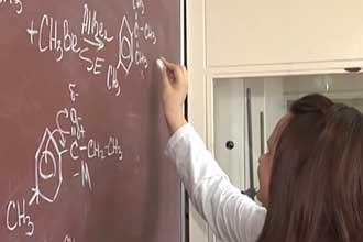 Пишет на доске химические формулы