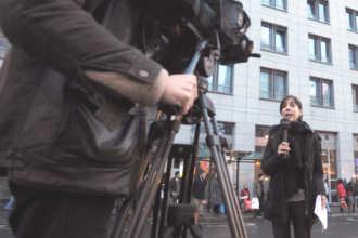 Журналистка снимает сюжет на улице города