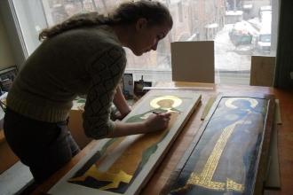 Девушка занимается реставрацией иконы
