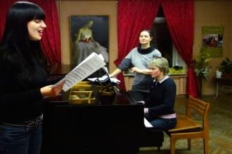 Девушка поет под аккомпанемент рояля