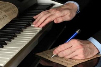 Мужчина записывает ноты в тетрадь