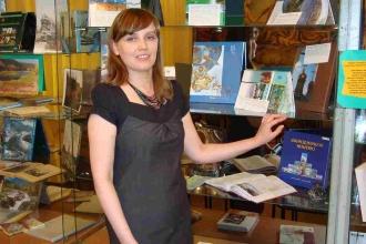 Девушка стоит возле стеллажа с книгами
