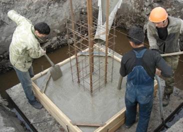 Фото: бетонщики заливают форму цементом