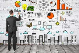 Человек рисует на стене различные маркетинговые штучки