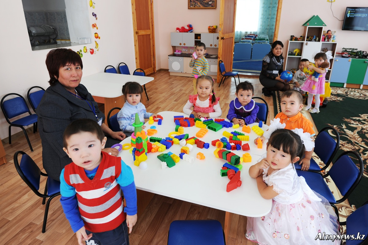 Учитель с детками на уроке дошкольного образования собирает лего