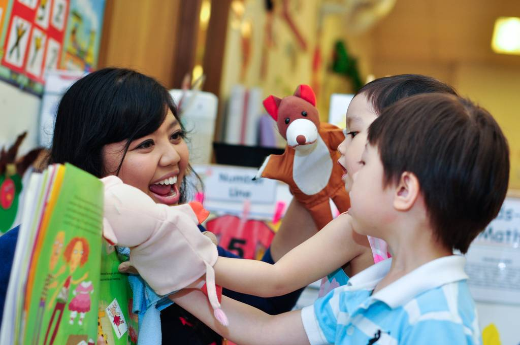 Педагог и дети в сингапурском детском саду