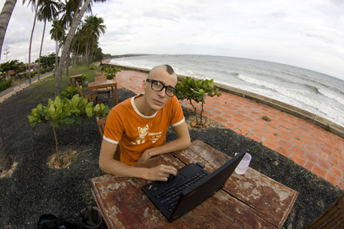 Молодой человек сидит за компьютером на берегу моря