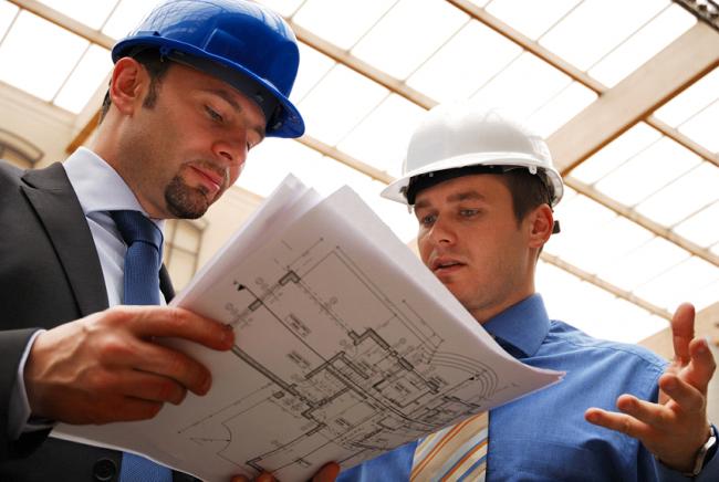 Специалисты-инженеры рассматривают план строительства