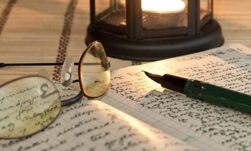 Тетрадь, очки и перо лежат на столе