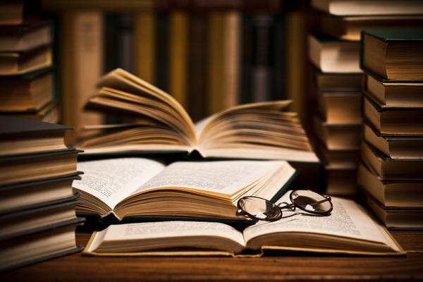 Раскрытые книги и очки лежат на столе