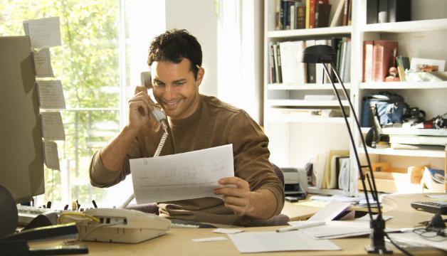 Мужчина изучает документ и разговаривает по телефону