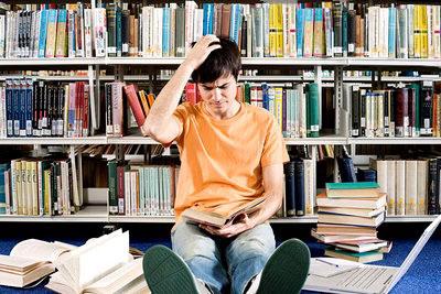 Молодой человек с книгой в библиотеке
