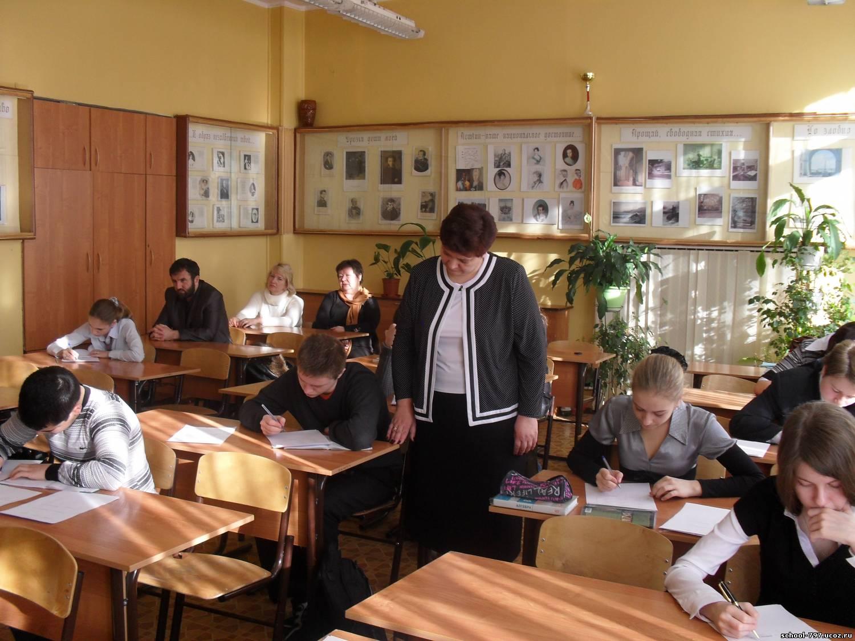 Учитель ходит между рядами парт, наблюдая за учениками