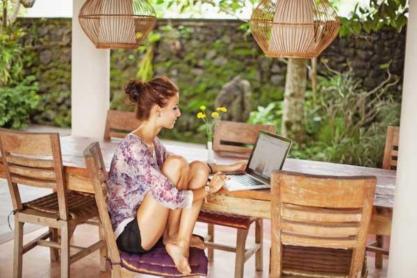 Девушка за ноутбуком в летней беседке