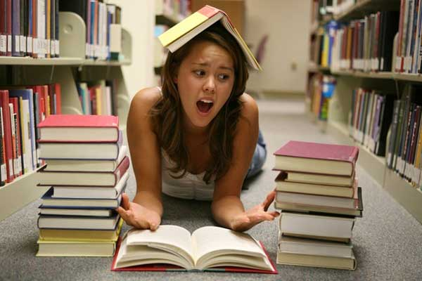 Девушка лежит на полу в окружении книг