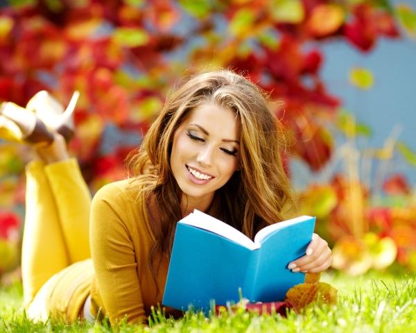 Девушка читает книгу, лежа на газоне