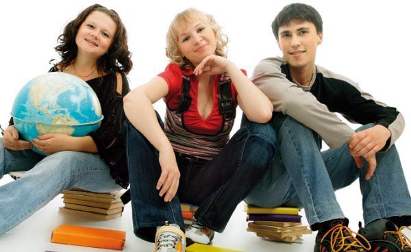 Две девушки и парень сидят на стопках с книгами