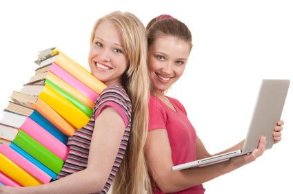 Две девушки стоят спиной друг к другу, с книгами и ноутбуком