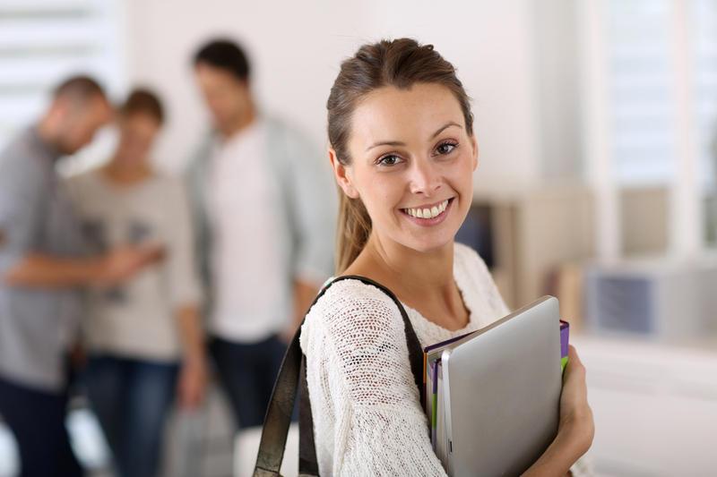 Улыбающаяся девушка держит в руках папки с документами