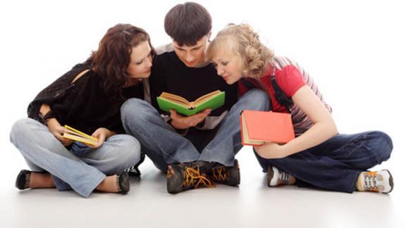 Девушки и парень читают книгу